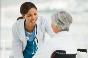 Young smiling doctor consoling patient sitting on wheel chair outdoor